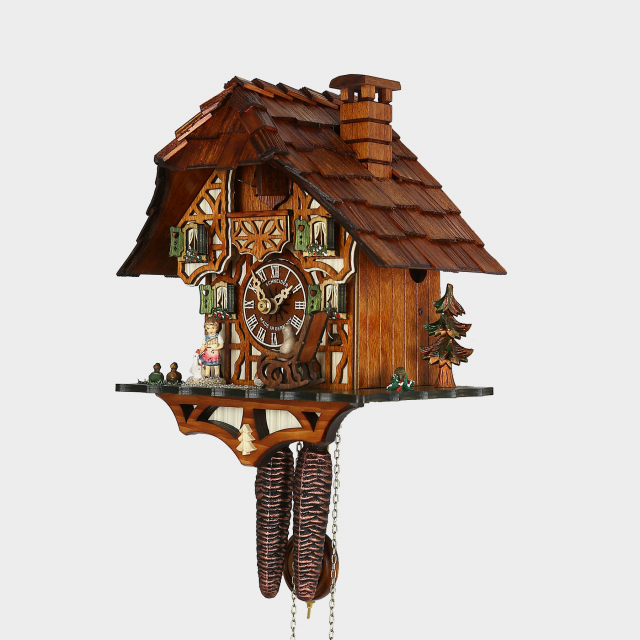 a housecat is rocking in the rocking chair on this original black forest cuckoo clock with
